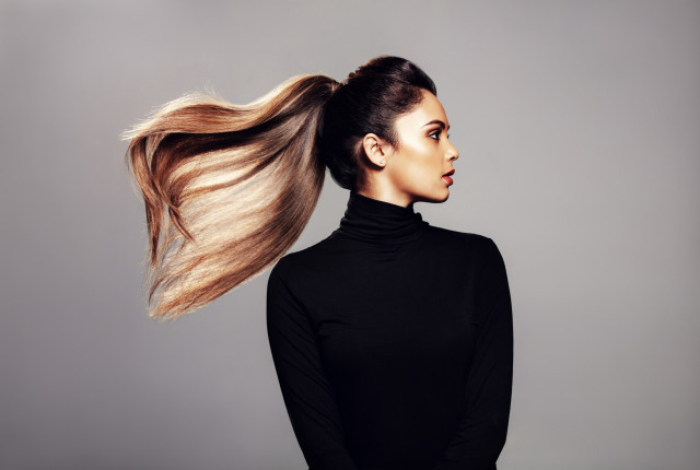 Studio shot of stylish young woman with flying hair against grey background. Female fashion model with long hair.